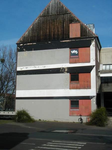 Foto von einem heruntergekommenen Gebäude. In der zweiten Etage ein Hinweisschild mit dem Text »VHS«