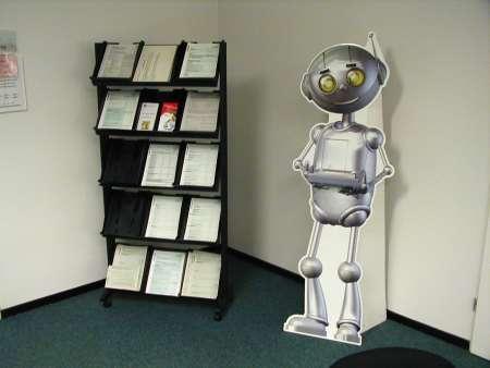 Ein Pappaufsteller, der Broschüren in einer Behörde anbietet, in Form eines Roboters