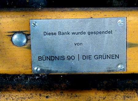 Hinweistafel auf der verdreckten Bank: Diese Bank wurde gespendet von BÜNDNIS 90 | DIE GRÜNEN