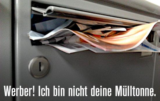 Mit Reklame bis zum Rand gewaltsam vollgestopfter Briefkasten. Darunter der Text: Werber! Ich bin nicht deine Mülltonne.