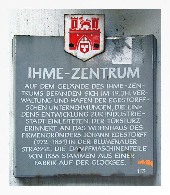 Schild, das im Ihmezentrum hing, bevor es von Carlyle zum Lindenpark umgebaut wurde, aber so, dass nur eine Ruine zurückblieb -- Ihme-Zentrum -- Auf dem Gelände des Ihme-Zentrums befanden sich im 19. Jh. Verwaltung und Hafen der Egestorffschen Unternehmungen, die Lindens Entwicklung zur Industriestadt einleiteten. Der Türsturz erinnert an das Wohnhaus des Firmengründers Johann Egestorff (1772-1834) in der Blumenauer Straße. Die Dampfmaschinenteile von 1886 stammen aus einer Fabrik auf der Glocksee